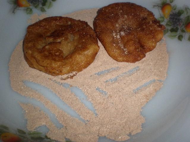 Pasar las torrijas de manzana por azúcar y canela